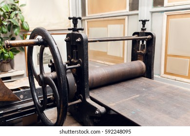 Old printing press in museum, historical exhibition. Close-up of ancient paper printing machine, printery exponent. Gallery with showpieces on background