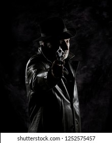 An old private detective armed with a vintage revolver in front of a black textured backdrop.