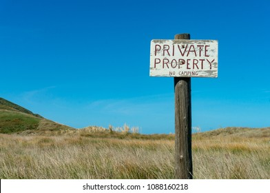 Old private property sign at beach