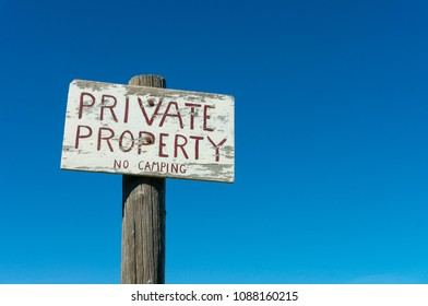 Old private property sign with blue sky