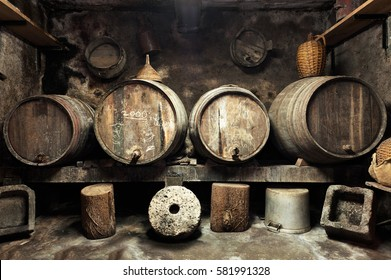 Old private wine cellar with many oak barrels, equipment for wine production. Old oak barrels in cellar.