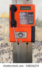Old public pay phone at Jerusalem, Israel. View on the Temple Mount, Dome of the Rock mosque and Wailing Wall at Old city in the blur background