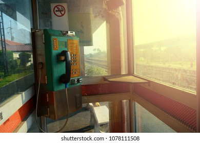old public phone booth with stain of dust and the signs of no smoking with sunlight in the morning at train station
