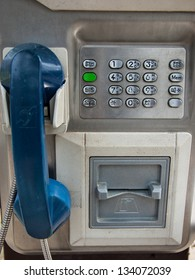 Old public telephone with blue receiver.