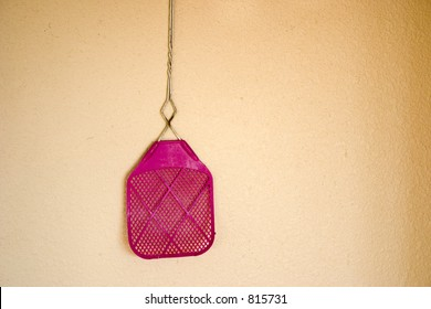 A old purple fly swatter is hanging on a wall