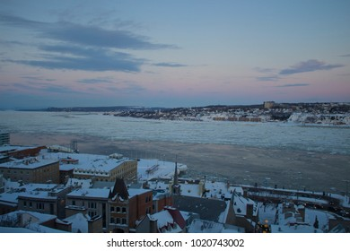 Old Quebec city at sunset, overlooking fast moving ice floes in the St Lawrence River.