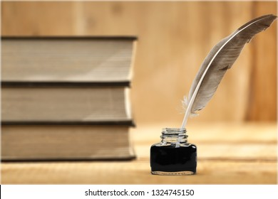 Old quill pen, books and vintage inkwell