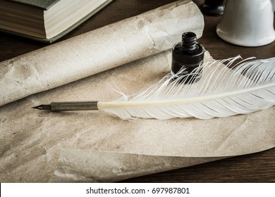 Old quill pen on the old paper. Letter writing. Historical atmosphere.