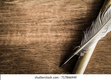 Old quill pen with old paper scroll on the dark wooden table. Letter writing. Historical atmosphere.