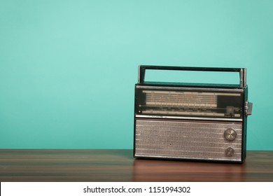Old radio on table in front of green background. Vintage style photo