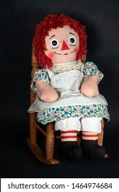 old rag doll with white apron sitting in a wooden rocking chair