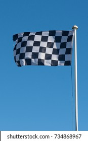old and ragged checkered flag pole against blue sky waving at full extent