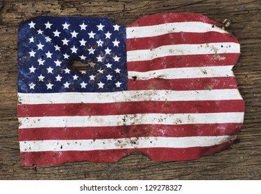 Old ragged flag of the United States of America. All on wooden background.