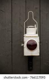 An old Railway lamp on a wooden door