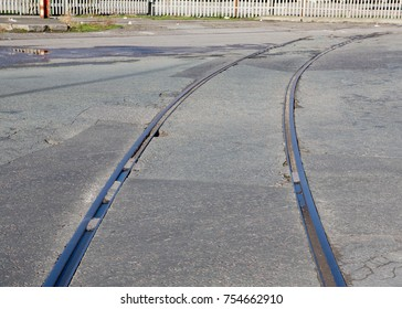 Old railway lines crossing the road surface at a Liverpool dock, UK.
