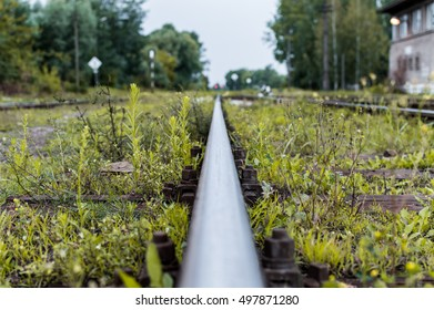 Old railway tracks and gravel leading into the infinite distance with selective focus
