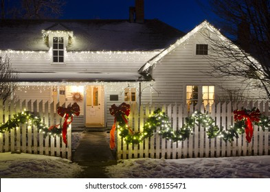 An old ranch house, complete with white picket fence, is decked out in Christmas lights, ribbons and garlands.  A Christmas tree in the window sets the scene for a romantic country Christmas.