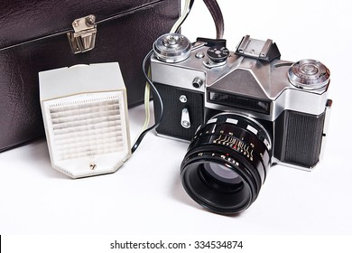 Old range finder vintage photo camera with flash isolated on white. Old camera flash with a leather case isolated on a white background.