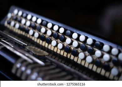 The old rare accordion buttons close up view. Low light photo.