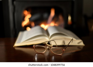 Old Reading Glasses On Old Book And Fireplace