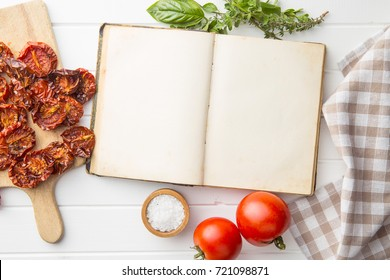 Old recipe book with tomatoes, dried tomatoes, herbs and salt. Top view on cookbook.