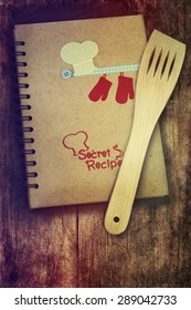 Old recipe notebook and spoon on wood background.