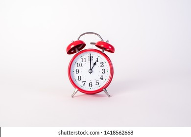 Old red alarm clock isolated on white background at one o'clock