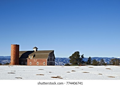 Old Red Barn on Top of Hill in on a Snow Covered Mountain in Winter