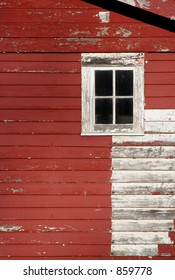An old red barn, paint peeling badly. Window and area that was painted white, also peeling.