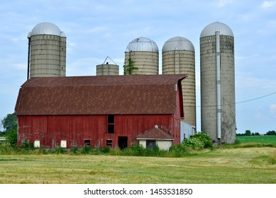 An old red barn with silos behind and cut grasses in the foreground on an early morning summer day with clouded blue skies.
