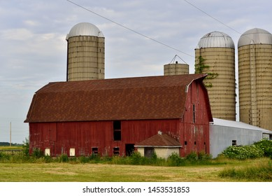 An old red barn with silos behind and cut grasses in the foreground on an early morning summer day with clouded skies.
