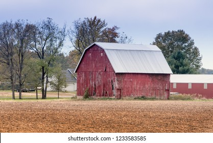 an old red barn sits on the family farm, beside a just cut field. Agriculture in the midwest USA.