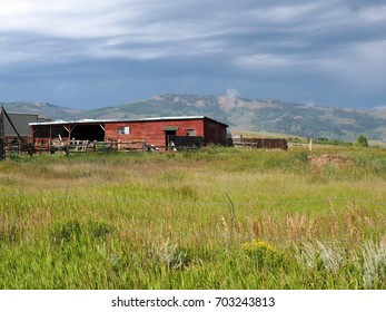 An old red barn sits on a prairie in Colorado with the mountains in the background.