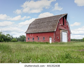 old red barn surrounded by green grass
