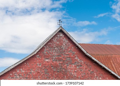 Old Red Barn with traditional roster weather vane and peeling paint in the rural countryside