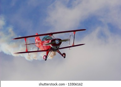An old red biplane in air show .