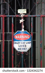 """Old red and blue security gate with signage reading """"warning crazy cat lady lives here"""""""