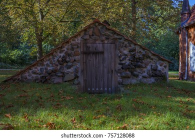 Old red brick building with old stone walls and wooden door in autumn with trees surrounding