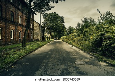 Old red brick houses along the used asphalt road.