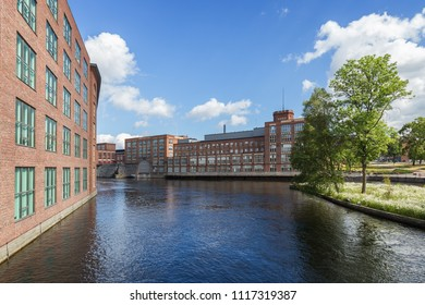 Old red brick industrial buildings along the Tammerkoski rapids in downtown Tampere, Finland on a sunny day.