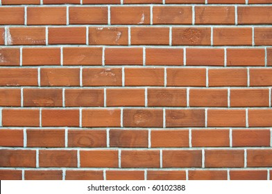 Old red brick wall background with uneven structure