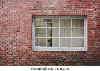 old red brick wall texture background with classic white wooden frame and sash window with glass panels, copy space, vintage effect