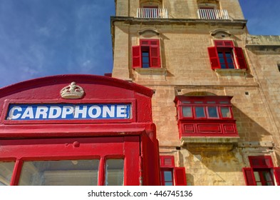 An old red cardphone booth in the historic city Valletta with an old appartment building in the background