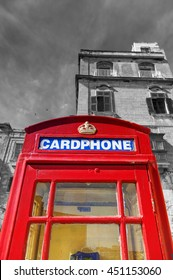 An old red cardphone booth in the historic city Valletta with an old apartment building in the background, with black and white background for a higher booth contrast