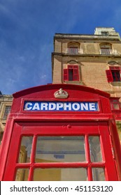 An old red cardphone booth in the historic city Valletta with an old apartment building in the background