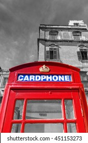An old red cardphone booth in the historic city Valletta with an old apartment building in the background, with black and white background and glass for a higher booth contrast