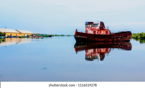 An old red color boat at the backwaters of fishing area in Pondicherry harbor, Pondicherry (Puducherry), India
