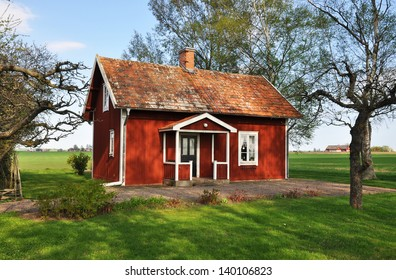 Old red cottage surrounded by farmland.