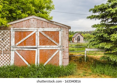 Old red farm sheds with a horse peaking out of the back one