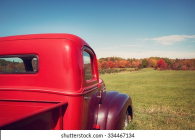 Old red farm truck against apple orchard and autumn landscape background. Vintage filter effects.